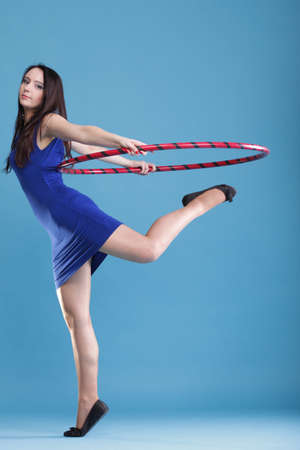 Beautiful woman in a sport wear. Dance hoop gym exercises\ blue background