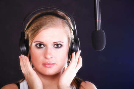 woman girl is singing rock song with a microphone headphones photo