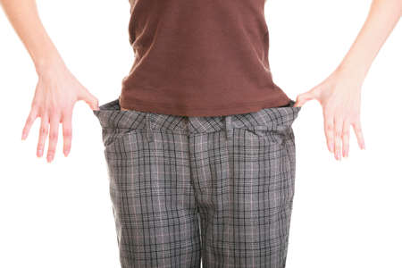 Woman showing how much weight she lost. Healthy lifestyles concept isolated photo