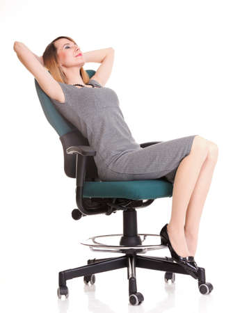 Full length of young business woman sitting on the chair over white background relaxing photo