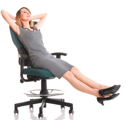 Full length of young business woman sitting on the chair over white background relaxing Stock Photo
