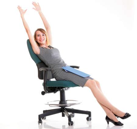 Longitud total de la mujer de negocios joven sentado en el portapapeles silla sosteniendo sobre fondo blanco relajarse