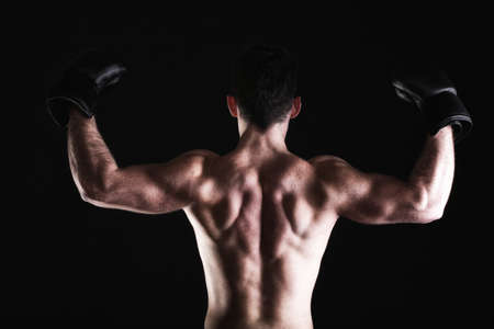 Boxer raising his arms strong athletic muscle man, sports guy showing his muscles male back isolated on black background