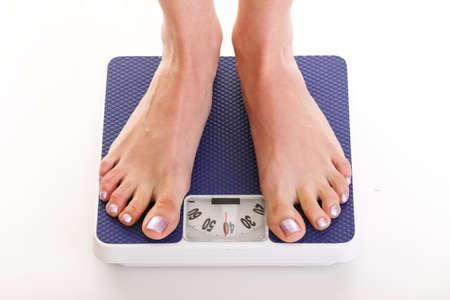 Donna piedi e la scala del peso blu isolato su sfondo bianco