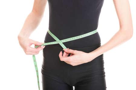 Atractiva mujer joven atl�tico y sexy medir el tama�o de su cintura con una cinta m�trica, aisladas sobre fondo blanco.
