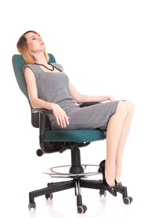 Full length of young business woman sitting on the chair over white background relaxing Standard-Bild