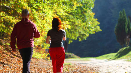 Woman and man walking cross country and trail in autumn forest Standard-Bild