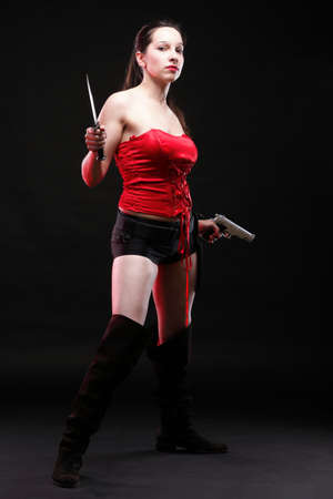 Sexy young woman in red with a gun and knife on black background photo