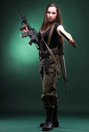 Bella mujer con ni�a de rifle de pl�stico Militar del Ej�rcito mantiene de fondo verde Gun
