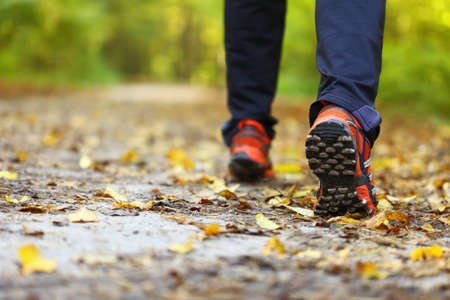 man walking cross country and trail in autumn forest photo