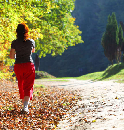 Woman and man walking cross country and trail in autumn forest Foto de archivo