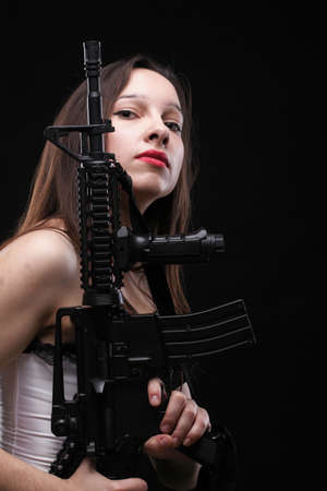 Sexy women - Girl holding an Assault Rifle, black background photo
