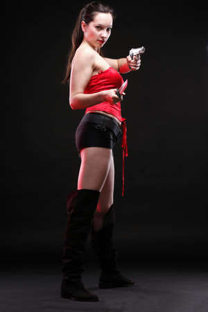 Sexy young woman in red with a gun and knife on black background Stock Photo - 13151785