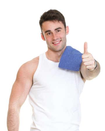 Saludable pulgar feliz hombre joven con una toalla sobre fondo blanco Foto de archivo