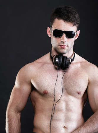 sexy headphones: handsome man listening to music on headphone black background