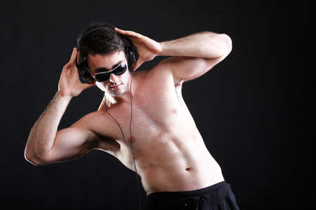 handsome man listening to music on headphone black background photo