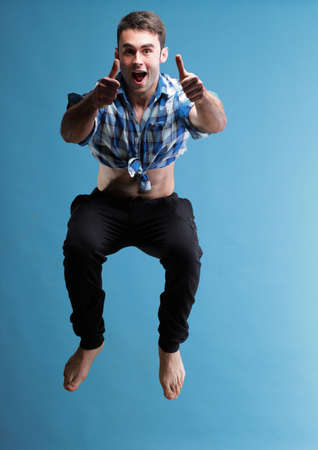 Young sport man jumping over blue background Stock Photo