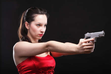Sexy young woman in red with a gun on black background Stock Photo - 13356962