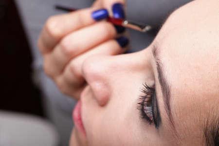 Woman applying eyeshadow using professional makeup brush photo