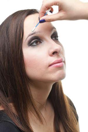 Woman applying eyeshadow makeup brush isolated on white photo