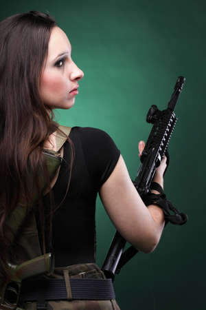 army uniform: Beautiful woman with rifle plastic Military Army girl Holding Gun green background Stock Photo