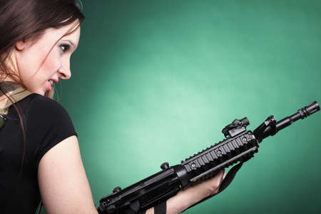 Beautiful woman with rifle plastic Military Army girl Holding Gun green background Stock Photo