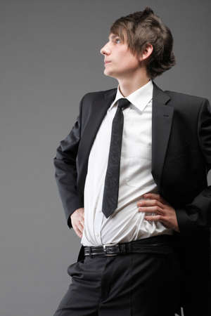 Fashion young businessman black suit casual tie on gray background photo