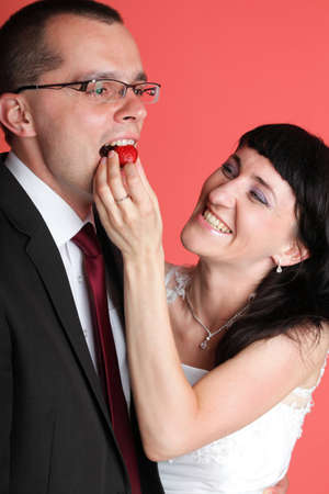 Happy smiling bride and groom young happy couple playfully eating strawbery on red background photo