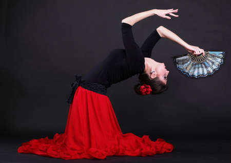 Attractive spanish dancer over black background young woman dancing flamenco