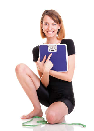 Caucasian young woman weight scale looking at the camera over white background photo