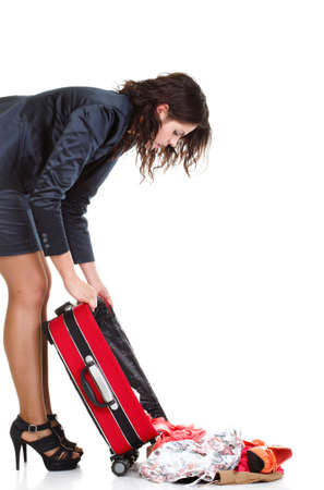 misadventure: Full length of young business woman to late mishap misadventure pulling red travel bag clock isolated on white background
