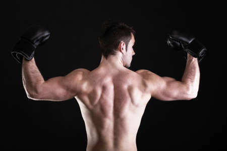 Boxer raising his arms strong athletic muscle man, sports guy showing his muscles male back isolated on black background photo