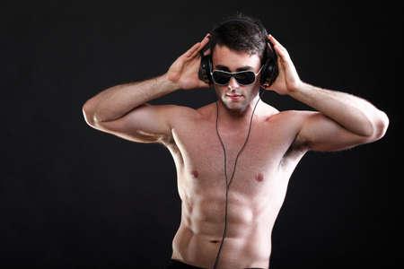 hombre guapo escuchar m�sica en auriculares fondo negro