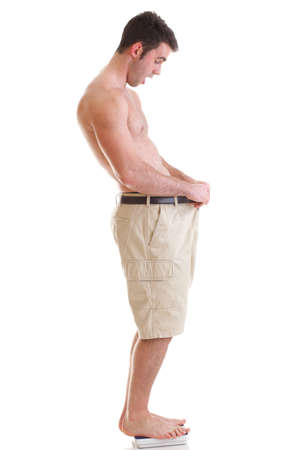 A young man looking down at his pants when he was fat. lost some weight Isolated on white.