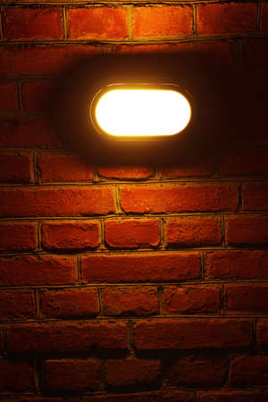 Old red brick wall with street light background photo