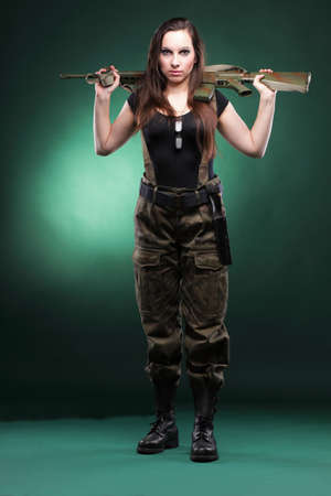 military uniform: Beautiful woman with rifle plastic Military Army girl Holding Gun green background Stock Photo