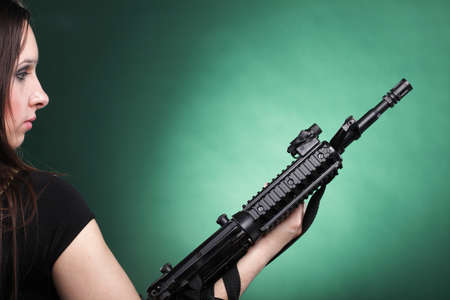 Beautiful woman with rifle plastic Military Army girl Holding Gun green background Stock Photo - 13258889