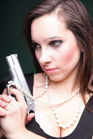 Sexy young woman with a gun, pearl on green background photo