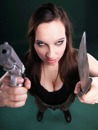 Sexy young woman in red with a gun, knife on green background Stock Photo - 13258880