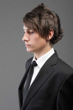conceited: Fashion young businessman black suit casual tie on gray background