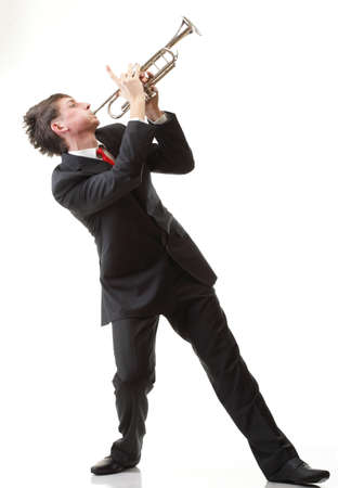 Portrait of a young man playing his Trumpet plays isolated white background photo