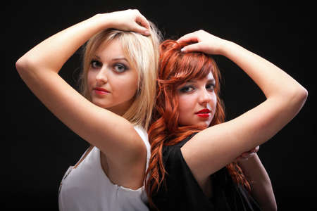 two happy young girlfriends blonde and red-hair black background Glamour photo