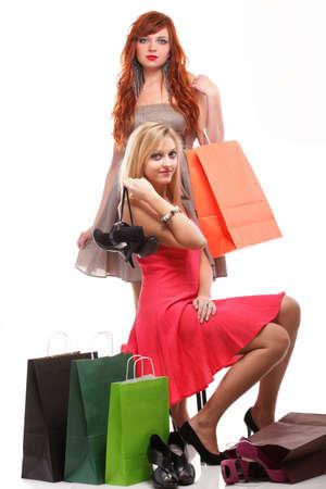 due ragazze felici zenzero e bionda con le scarpe di shopping borse su bianco
