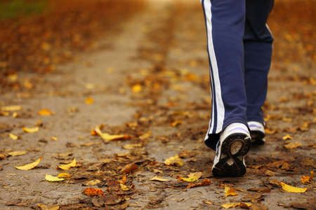 Woman walking cross country and trail in autumn forest photo