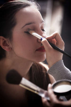 beautiful young brunette woman applying powder with a brush photo