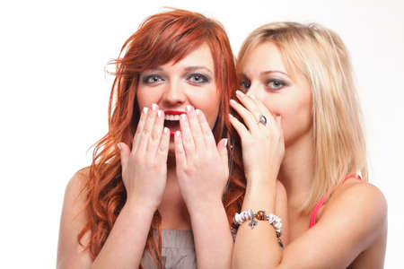 two happy young girlfriends blond and ginger talking white background - society gossip, rumor, rumour photo