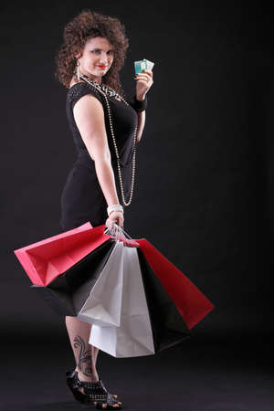 lovely woman with shopping bags over black background photo