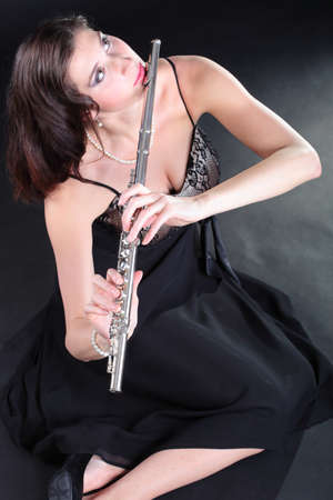 girl woman plays the flute on a black background photo