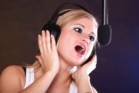 woman girl is singing rock song with a microphone headphones Stock Photo - 13389597