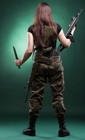Beautiful woman with rifle plastic Military Army girl Holding Gun green background photo